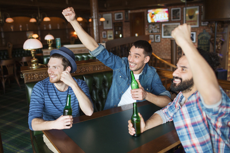 pubs: people, leisure, friendship and bachelor party concept - happy male friends drinking bottled beer and raised hands rooting for football match at bar or pub