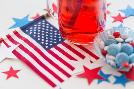 american independence day, celebration, patriotism and holidays concept - close up of juice glass, flag and candies at 4th july party