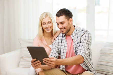 family sofa: love, family, technology, internet and happiness concept - smiling happy couple with tablet pc computer at home Stock Photo