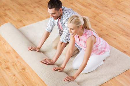 mensen, reparatie en renovatie concept - gelukkig paar ontrollen tapijt of tapijt op de vloer thuis Stockfoto