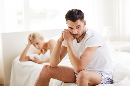 quarrel: people, relationship difficulties, conflict and family concept - unhappy couple having problems at bedroom Stock Photo