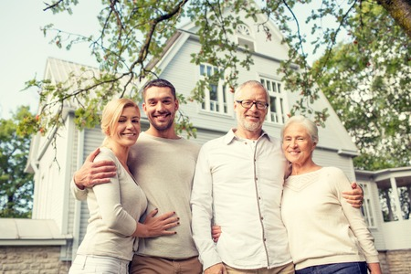 father and son: family, happiness, generation, home and people concept - happy family standing in front of house outdoors Stock Photo