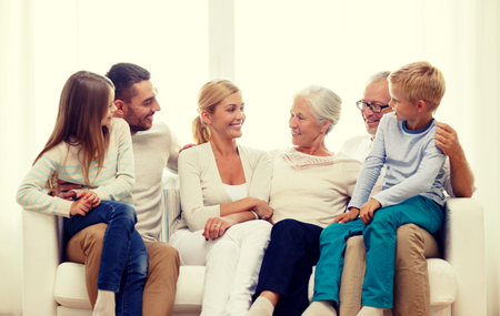 family couch: family, happiness, generation and people concept - happy family sitting on couch at home