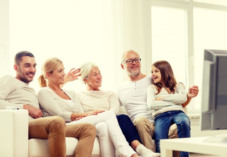 family, happiness, generation and people concept - happy family sitting on sofa and watching tv at home Archivio Fotografico