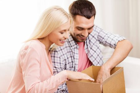 parcel: people, delivery, shipping and postal service concept - happy couple opening cardboard box or parcel at home