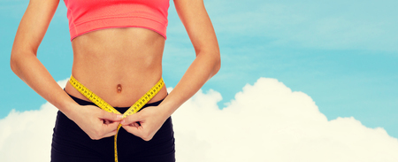 woman diet: diet, sport, fitness and heath concept - close up of female hands measuring waist with measuring tape