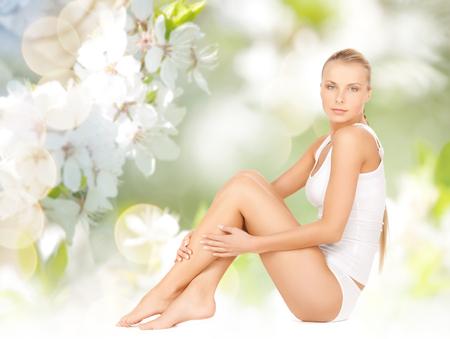 cuerpo humano: la gente, la belleza y el cuidado del cuerpo concepto - hermosa mujer en ropa interior de algodón piernas tocando sobre fondo verde flor de cerezo natural Foto de archivo