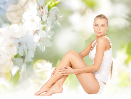 beautiful woman body: people, beauty and body care concept - beautiful woman in cotton underwear touching legs over green natural cherry blossom background Stock Photo