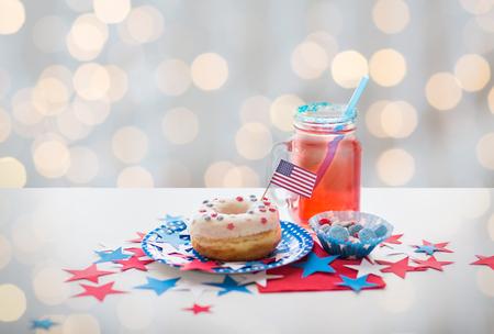 julio: día de la independencia americana, celebración, el patriotismo y el concepto de vacaciones - cerca de buñuelo dulce esmaltado con la bandera y los caramelos en vajillas en partido del 4 de julio por las luces de fondo