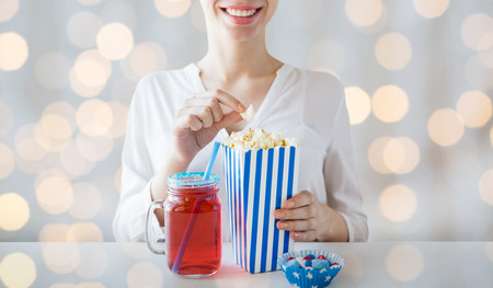 red and blue: american independence day, celebration, patriotism and holidays concept - close up of woman eating popcorn with drink in glass mason jar and candies at 4th july party over lights background