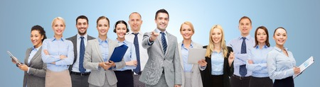 co workers: business, people, corporate, teamwork and office concept - group of happy businesspeople pointing at you over blue background