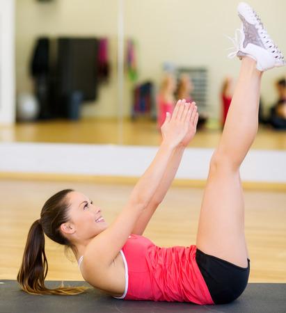 体育館でマット運動をしている女性の笑顔 - フィットネス、スポーツ、トレーニング、ジムやライフ スタイルのコンセプト