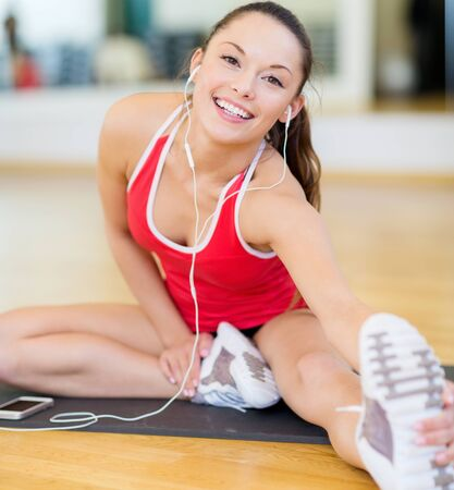 fitness gym: fitness, sport, training, gym, technology and lifestyle concept - smiling teenage girl with smartphone and earphones in gym Stock Photo