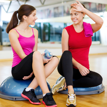chatting: fitness, sport, training, gym and lifestyle concept - two smiling women sitting on the half ball and relaxing after class in the gym
