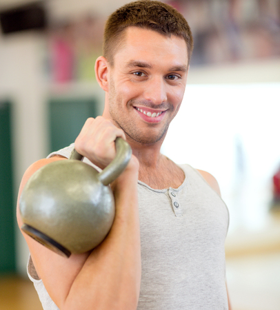musculine: fitness, sport, training, gym and lifestyle concept - smiling man with kettlebell in gym