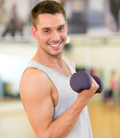 musculine: fitness, sport, training, gym and lifestyle concept - smiling man with dumbbell in gym