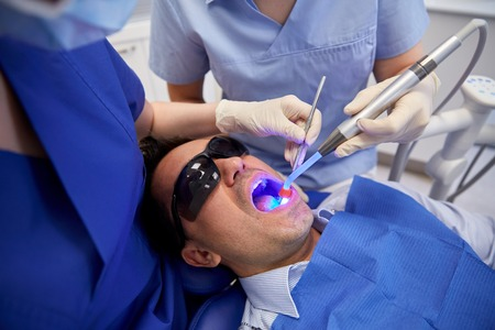 curing: people, medicine, stomatology and health care concept - female dentist and assistant with dental curing light and mirror treating male patient teeth at dental clinic office