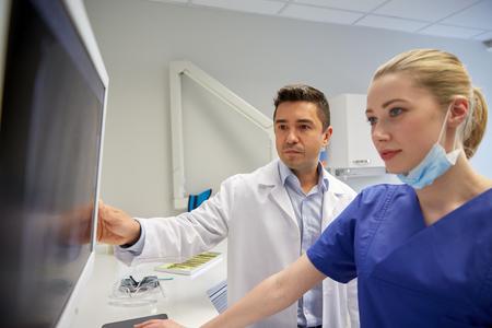 gezondheid: mensen, geneeskunde, tandheelkunde, technologie en gezondheidszorg concept - tandartsen op zoek naar x-ray scan op de monitor bij tandkliniek Stockfoto
