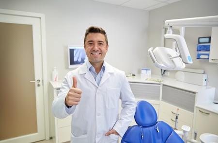 人、医学、口腔病学、ヘルスケアの概念 - 幸せの中間高齢男性歯医者は歯科オフィスで親指を現して白衣