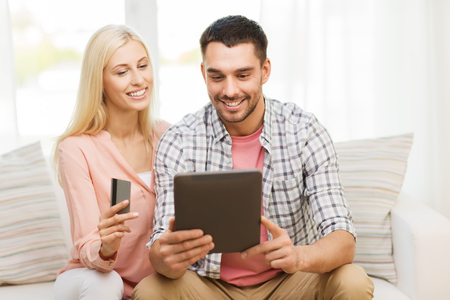 e money: technology, people, e-money and commerce concept - smiling happy couple with tablet pc computer and credit or bank card shopping online at home