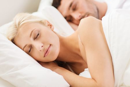 bed room: people, family, bedtime and happiness concept - happy couple sleeping in bed at home