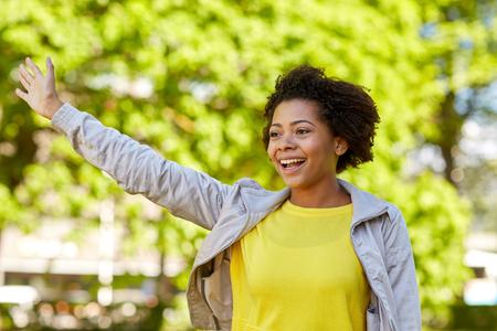 personas saludando: la gente, la raza, el origen étnico y el concepto gesto - African American feliz mujer joven agitando la mano en el parque de verano Foto de archivo