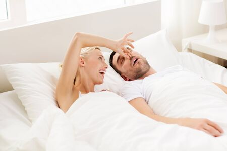 lovers in bed: people, family, bedtime and couple concept - happy woman closing nose to her snoring man sleeping in bed at home Stock Photo