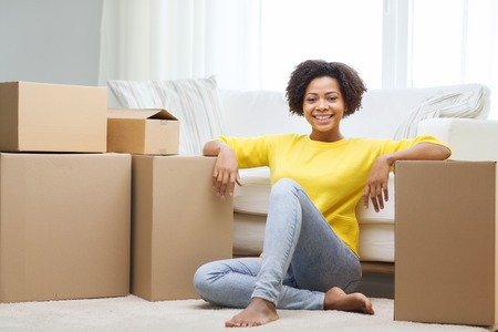 young woman smiling: people, moving new place and repair concept - happy african american young woman with many cardboard boxes sitting on floor at home Stock Photo