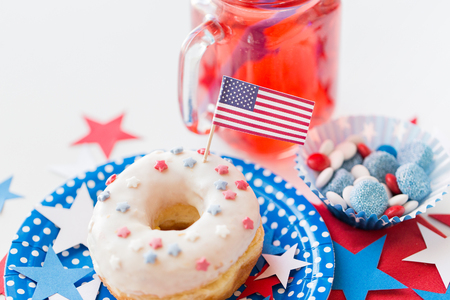 food state: american independence day, celebration, patriotism and holidays concept - close up of glazed sweet donut with flag and candies in disposable tableware at 4th july party