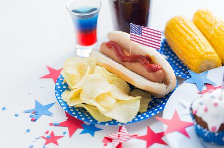 dog days: fiestas nacionales, celebración, comida y pattism concepto - cerca de perro caliente con el americano decoración bandera, papas fritas y bebidas el 4 de julio en la fiesta de Día de la Independencia