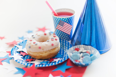 food state: american independence day, celebration, patriotism and holidays concept - close up of glazed sweet donut with juice and candies in disposable tableware at 4th july party