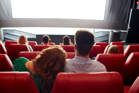 watching movie: cinema, entertainment, leisure and people concept - happy, couple watching movie in theater from back