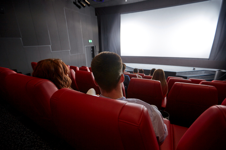 family movies: cinema, entertainment, leisure and people concept - couple watching movie in theater from back