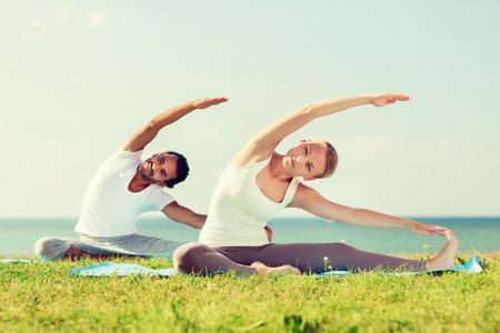 Fitness, Sport, Freundschaft und Lifestyle-Konzept - lächelnde Paar macht Yoga-Übungen sitzen auf Matten im Freien