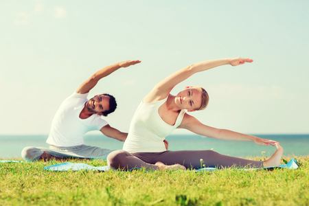 sea sports: fitness, sport, friendship and lifestyle concept - smiling couple making yoga exercises sitting on mats outdoors