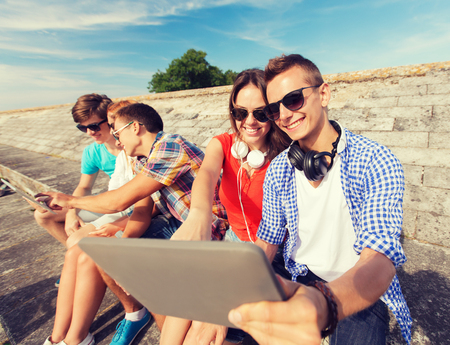 people watching: friendship, leisure, summer and people concept - group of smiling friends with tablet pc computers sitting outdoors Stock Photo
