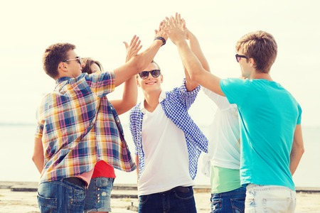 high: friendship, leisure, summer, gesture and people concept - group of smiling friends making high five outdoors