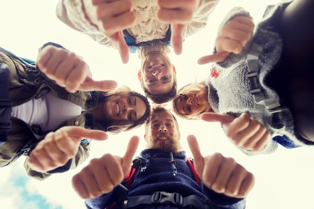 circle of friends: travel, tourism, hike, gesture and people concept - group of smiling friends with backpacks standing in circle and showing thumbs up outdoors Stock Photo