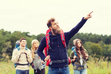 grupos de personas: aventura, viajes, turismo, ir de excursión y la gente concepto - grupo de amigos sonriendo con mochilas que apunta el dedo al aire libre