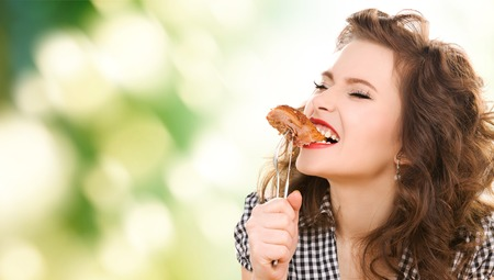 barbecue: people, diet and food concept - hungry young woman eating meat on fork over green natural background