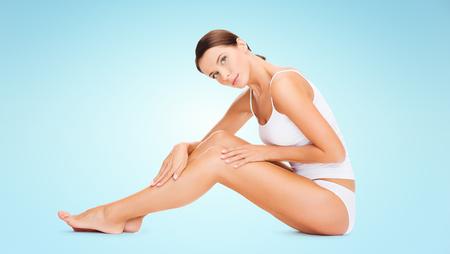 belles jambes: les gens, la beauté et soins du corps concept - belle femme en sous-vêtements de coton jambes toucher sur fond bleu