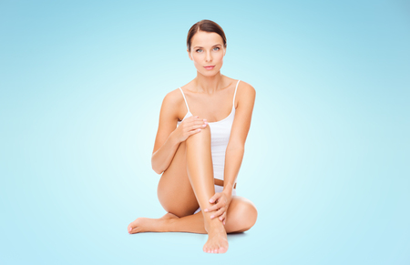 beauty body: people, beauty and body care concept - beautiful woman in cotton underwear touching legs over blue background Stock Photo