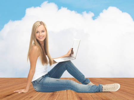 learning computer: people, technology, education and distant learning concept - happy student girl with laptop computer sitting on wooden floor over white cloud and blue sky background Stock Photo