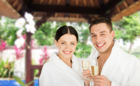 all smiles: people, travel, tourism, vacation and holidays concept - happy couple in bathrobes with champagne glasses over spa hotel resort background