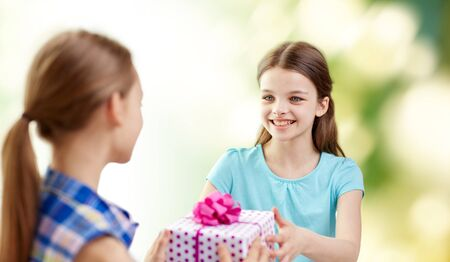 receiving: people, children, holidays, friends and friendship concept - happy little girls with birthday present over green background