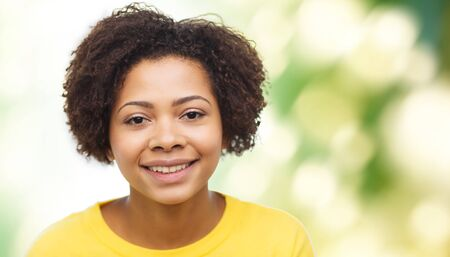african american woman: people, race, ethnicity and portrait concept - happy african american young woman face over green natural background Stock Photo
