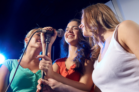 clubbers: party, holidays, celebration, nightlife and people concept - happy young women singing karaoke in night club