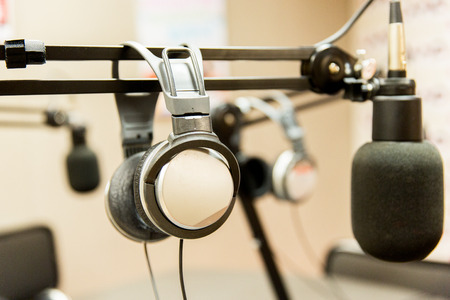 equipment: technology, electronics and audio equipment concept - close up of headphones and microphone at recording studio or radio station