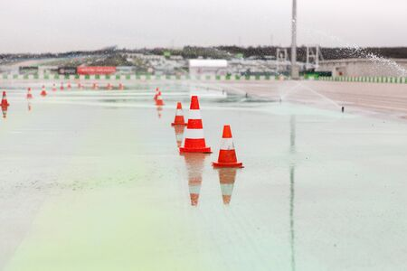 traffic cone: racing, motosports, extreme and motoring concept - traffic cones and sprinklers on wet speedway of stadium Stock Photo