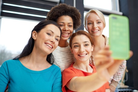 women friendship: people, leisure, friendship and technology concept - happy young women taking selfie with smartphone